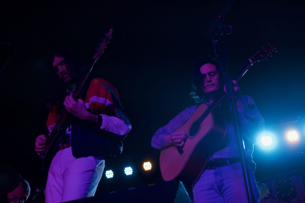 Two members of Shy Boys.  One with long brown hair wearing a red jacket and playing a bass guitar, the second with shoulder-length brown hair, a checked blue shirt, and an acoustic guitar.  The lighting is blue.