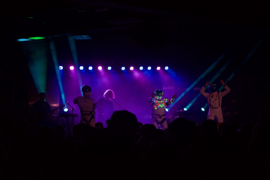 Members of STRFKR in a dimly lit backdrop, with three dancers dressed as astronauts in the foreground.