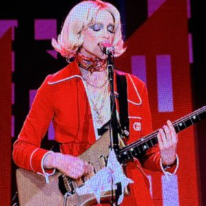 St. Vincent singing into their microphone at Ascend Amphitheater